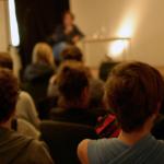 Menschen sitzen vor einer Bühne und hören einer Person zu.