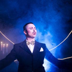 Mono steht vo einem Lichtkegel, trägt einen schwarzen Anzug mit weißem Hemd und goldener Fliege. Hinter ihm brennen 4 Kerzen und den Hintergrund durchziehen Nebelschwaden.