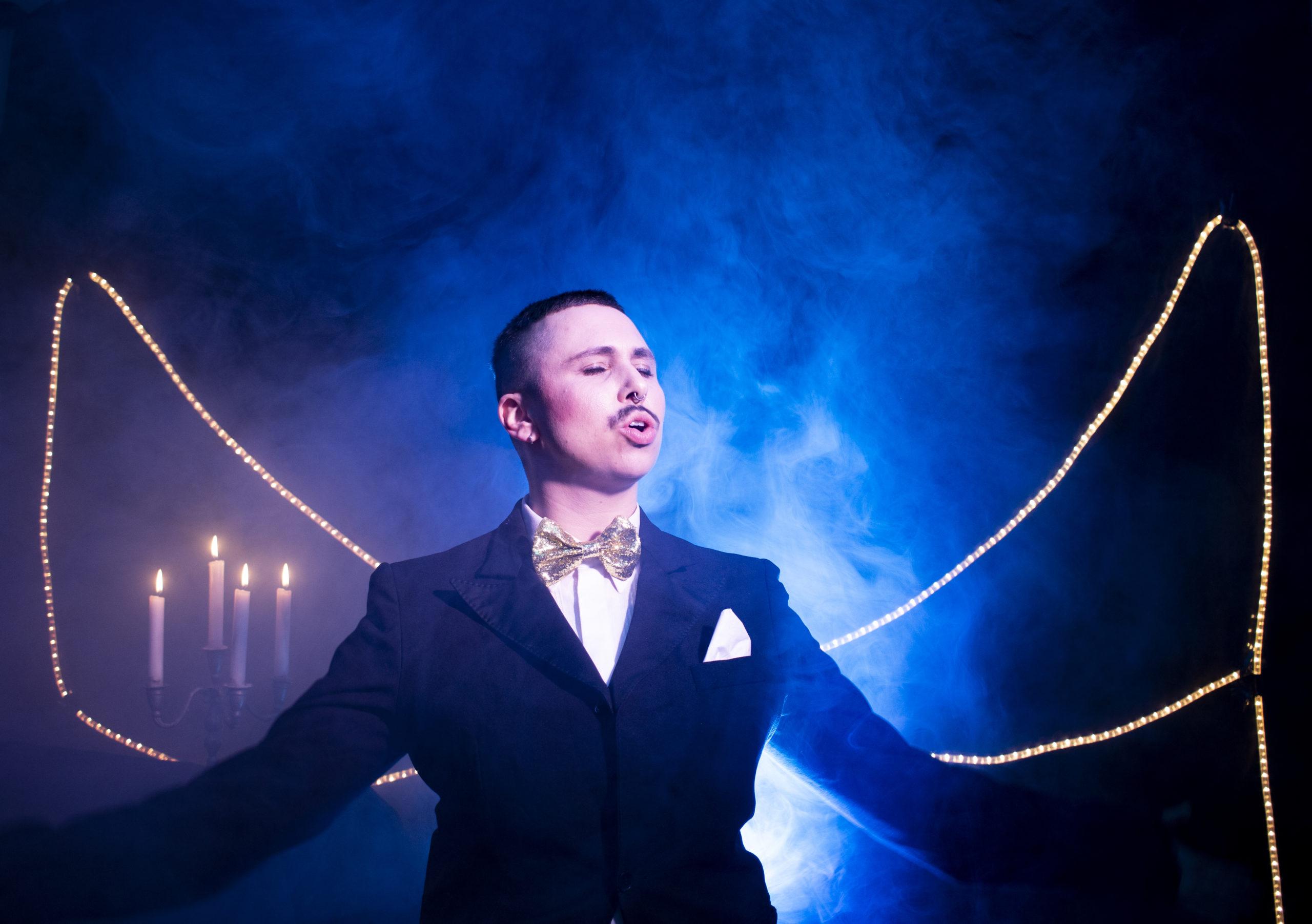 Mono steht mit geschlossenen Augen vor einem Lichtkegel, trägt einen schwarzen Anzug mit weißem Hemd und goldener Fliege. Hinter ihm brennen 4 Kerzen und den Hintergrund durchziehen Nebelschwaden.